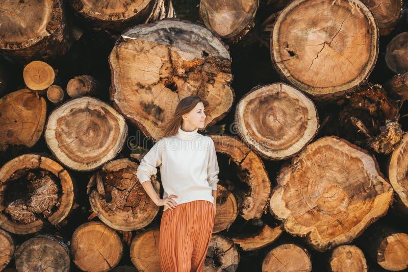 Hermosa mujer en el jersey blanco posa en el fondo de troncos de madera en el parque fotografía de archivo