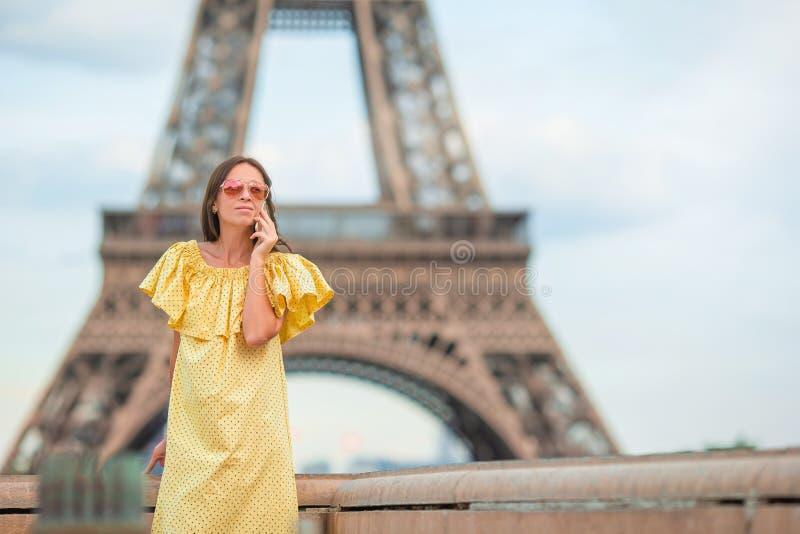 Hermosa mujer en París en el fondo de la torre Eiffel durante sus vacaciones foto de archivo