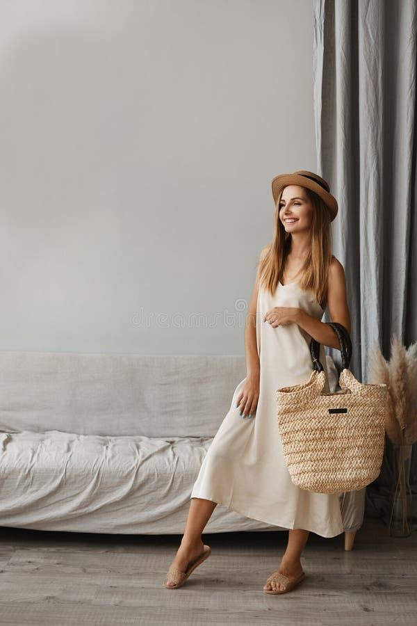 Hermosa mujer joven con un vestido ligero y gorra posando en el interior Chica modelo con vestido de verano ligero y con un gran fotografía de archivo libre de regalías