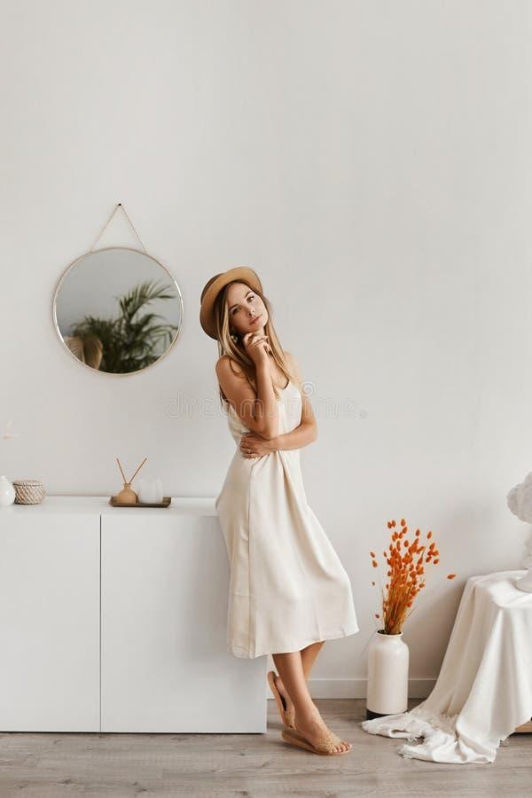 Hermosa mujer joven con un vestido ligero y gorra posando en el interior Mujer modelo vestida de verano y con una bolsa grande en fotografía de archivo libre de regalías