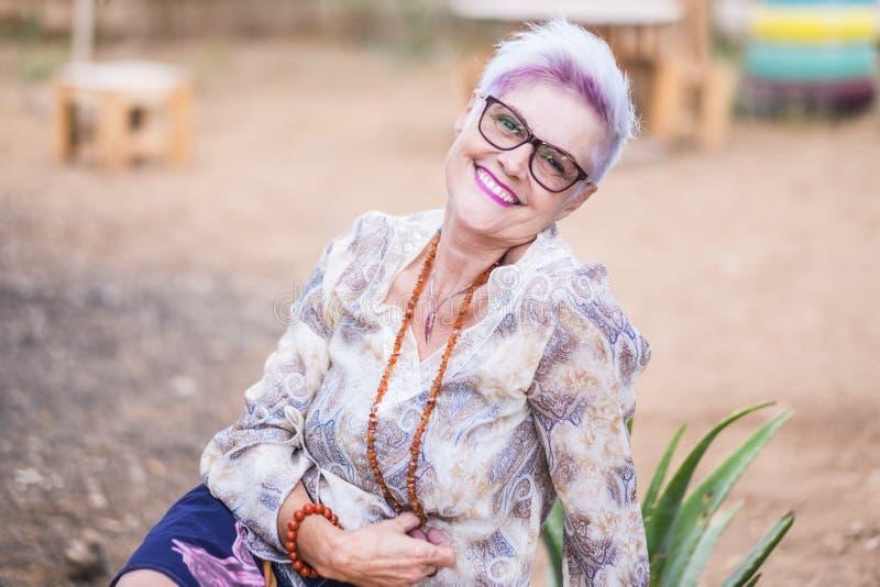 Hermosa mujer madura alternativa con hipster punk estilo hipster blanco y violeta sonrisa en la cámara posando para una fotografía de archivo