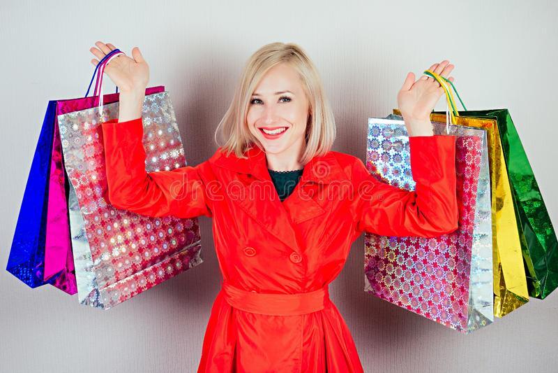 Hermosa mujer rubia y alegre, con un vestido verde con bolsas de compras en un fondo gris. Concepto de imagen de archivo libre de regalías