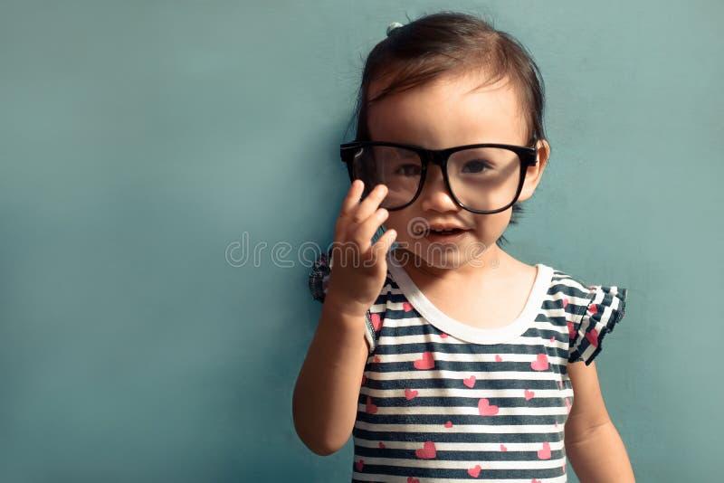Hermosa niña sonriente, chica con anteojos, fondo azul aislado con espacio para copiar foto de archivo