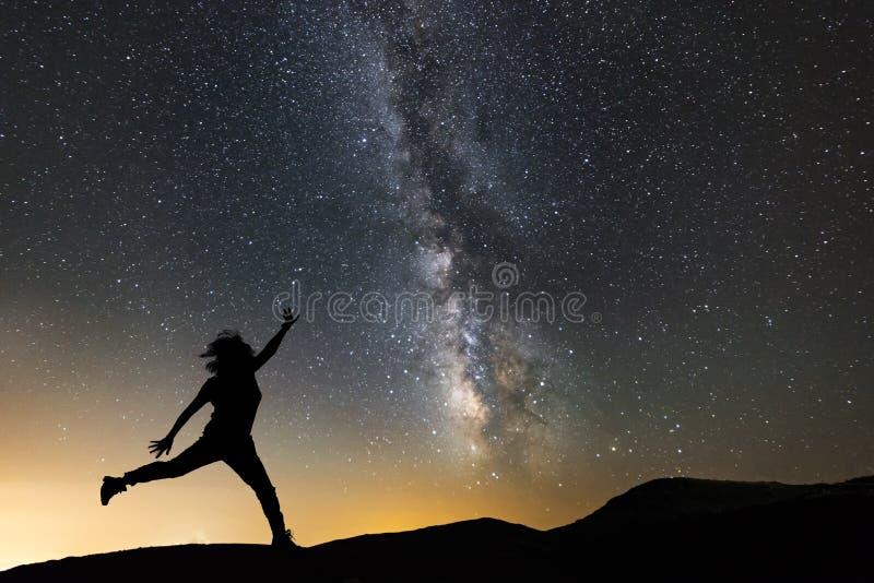 Hermosa noche estrellada, silueta hembra saltando sobre el fondo del camino lechoso Paisaje nocturno con galaxia de vía lechosa fotografía de archivo libre de regalías