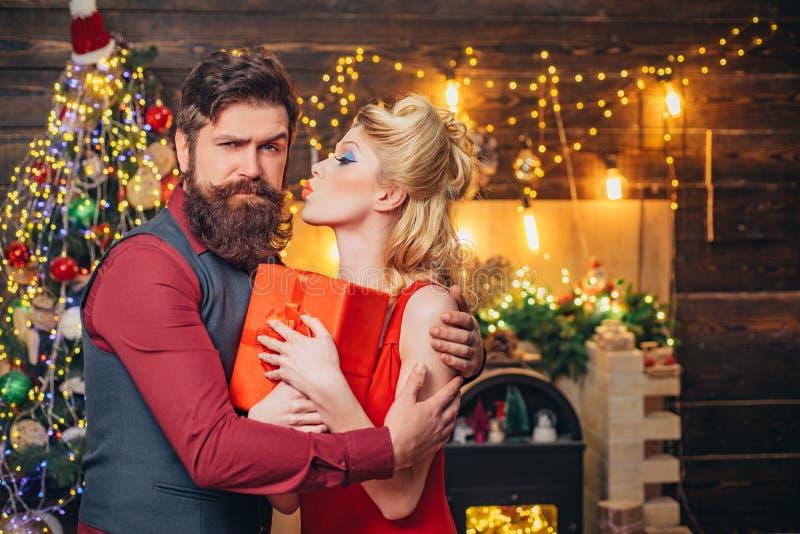 Hermosa pareja de Navidad sonriendo con regalo - le deseo Feliz Año Nuevo. Joven pareja de moda navideña. Gracioso imagen de archivo