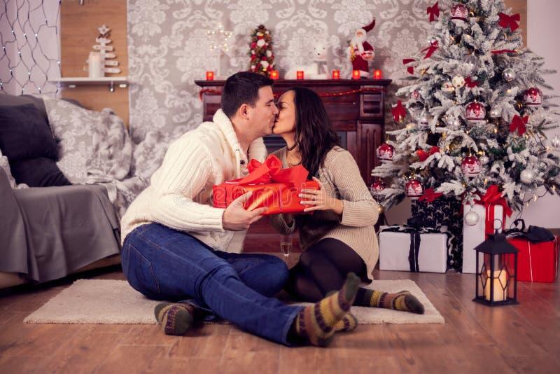 Hermosa pareja joven besándose cerca de un árbol de Navidad en un hogar acogedor foto de archivo libre de regalías