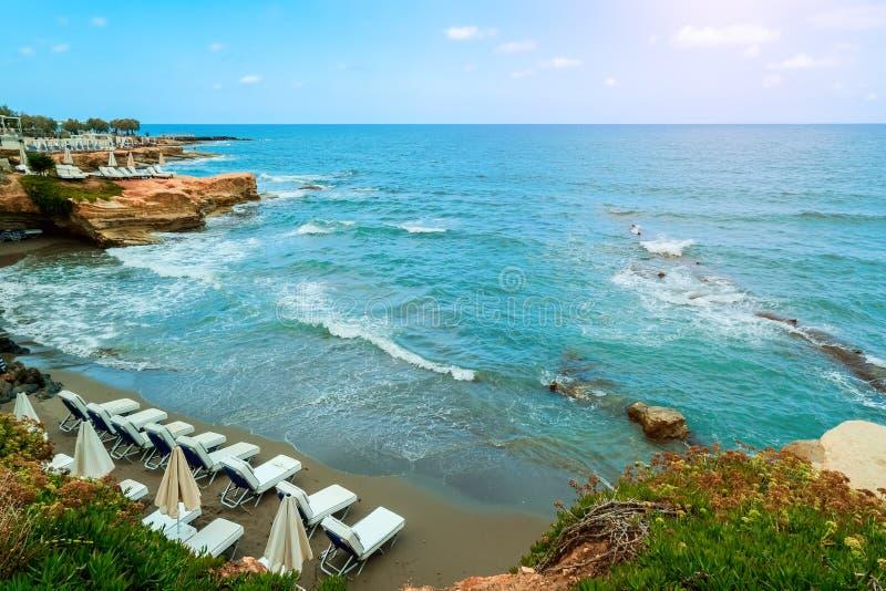 Hermosa playa con tumbonas blancas en una pequeña bahía foto de archivo