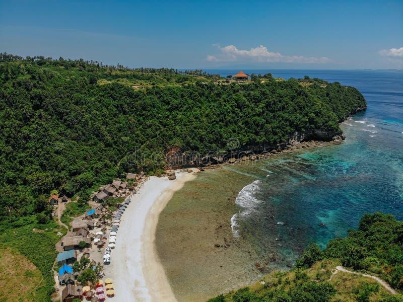 Hermosa playa de bahía con aguas turquesas del océano con muchos paraguas arriba foto aérea con playa blanca y selva tropical imagen de archivo libre de regalías