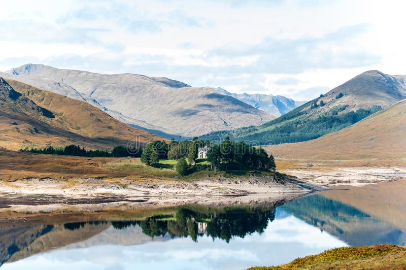 Hermosa vista con la casa escocesa en las montañas lago y bosque fotografía de archivo