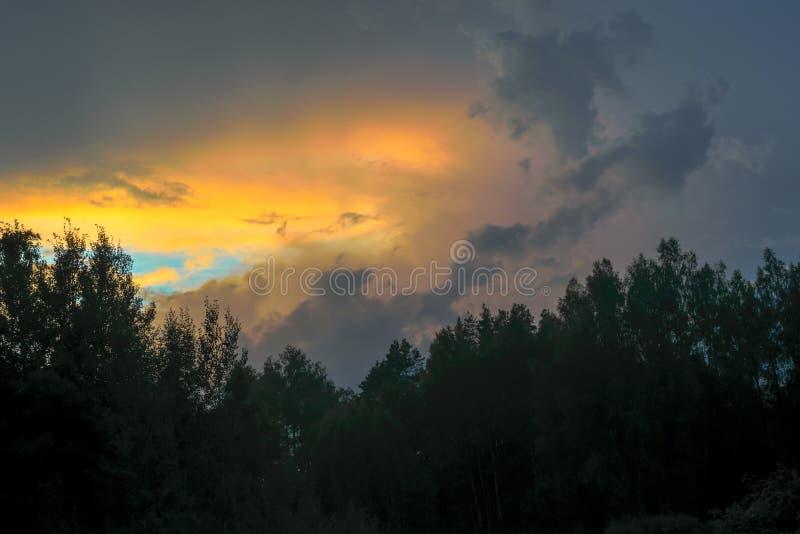 Hermosa vista de la formación de la nube de tormenta de la puesta del sol aclarada con los rayos de sol amarillos pasados y el ci foto de archivo libre de regalías