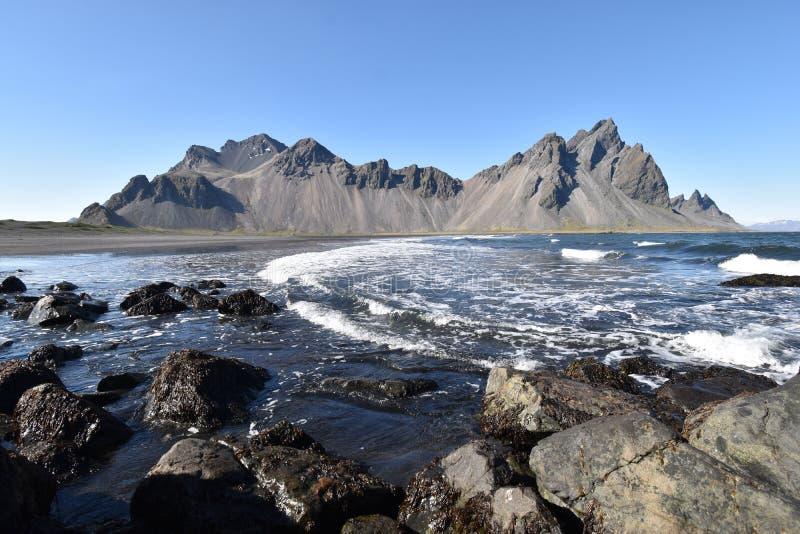 Hermosa vista de las montañas de Vestrahorn con la arena negra y el océano en frente cerca de Hoefn en Islandia fotografía de archivo