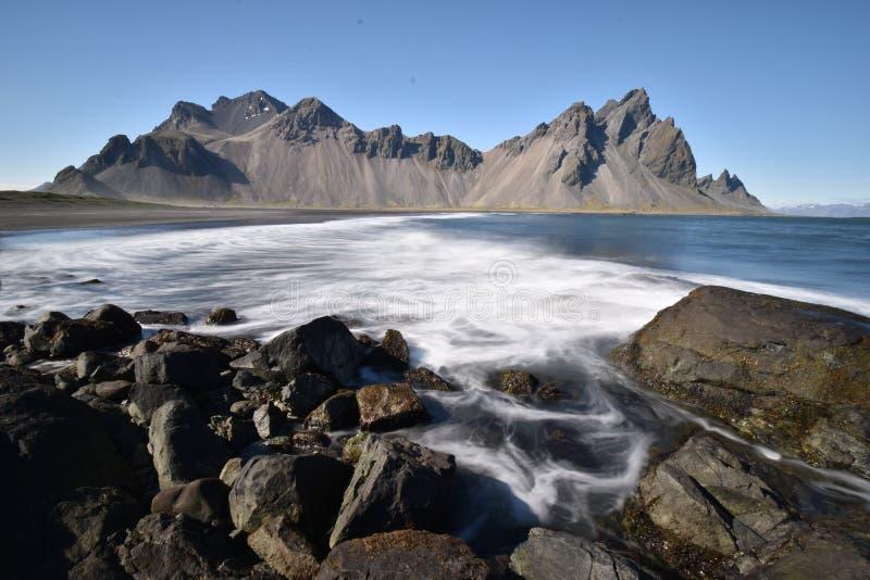 Hermosa vista de las montañas de Vestrahorn con la arena negra y el océano en frente cerca de Hoefn en Islandia fotografía de archivo libre de regalías