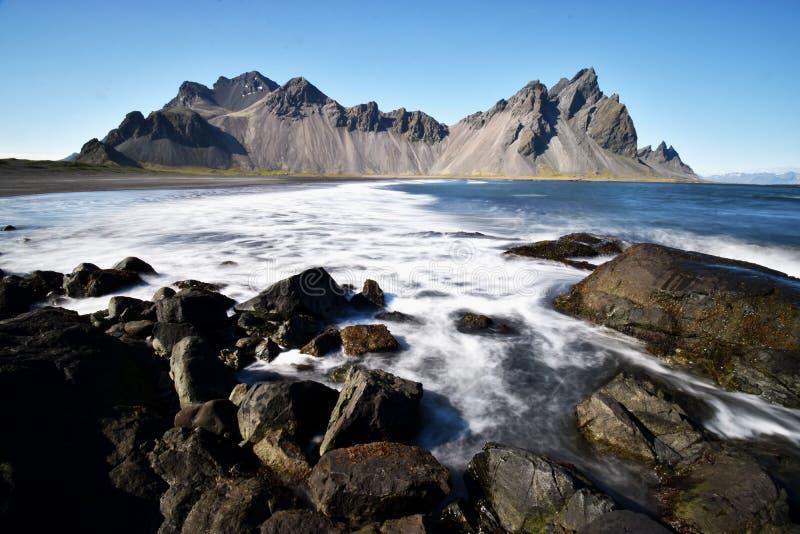 Hermosa vista de las montañas de Vestrahorn con la arena negra y el océano en frente cerca de Hoefn en Islandia imagen de archivo libre de regalías