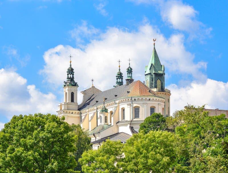 Hermosa vista de los árboles viejos y del cielo azul brillante, viejo centro de ciudad, Lublin Polonia del verde de la iglesia foto de archivo libre de regalías