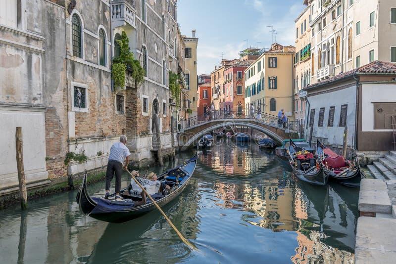 Hermosa vista de un canal veneciano típico, Venecia, Italia, con un par en una góndola, tomando imágenes y haciendo el vídeo imagen de archivo libre de regalías
