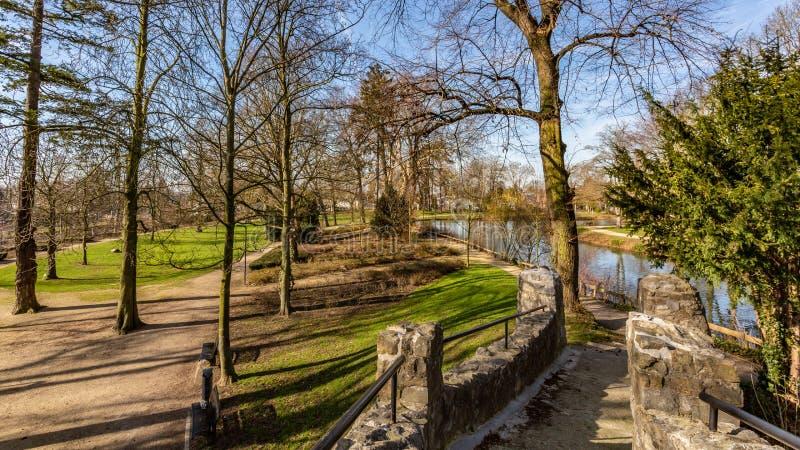 Hermosa vista de un puente de árboles, de un río, de la hierba verde y de los rastros en el parque de Proosdij imagenes de archivo