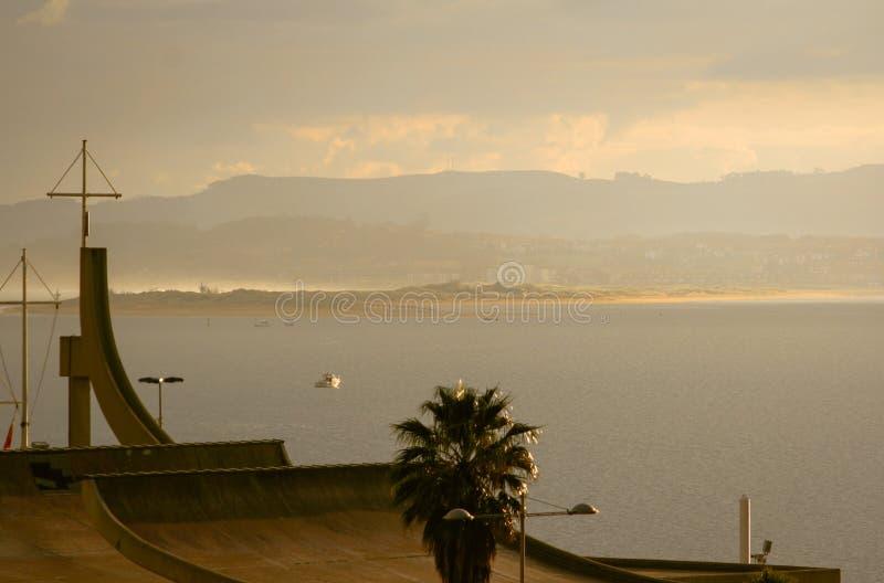 Hermosa vista de una puesta del sol en una 'promenade' con una playa en el fondo y la cordillera c?ntabra imagen de archivo