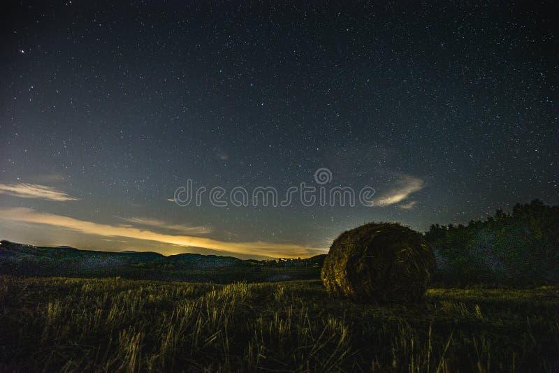 Hermosa vista del cielo nocturno protagonizado con las nubes sobre un campo cultivado con la bala de heno imágenes de archivo libres de regalías