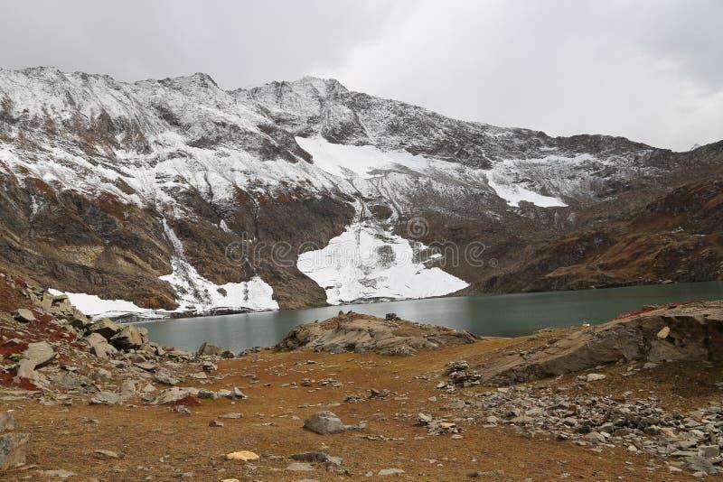 Hermosa vista del lago y de glaciares en la montaña debajo del cielo nublado foto de archivo libre de regalías