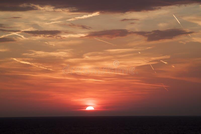 hermosa vista del sol que oculta detr?s de la superficie del mar su imagen de archivo libre de regalías