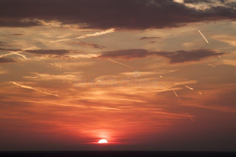 hermosa vista del sol que oculta detr?s de la superficie del mar su fotos de archivo libres de regalías