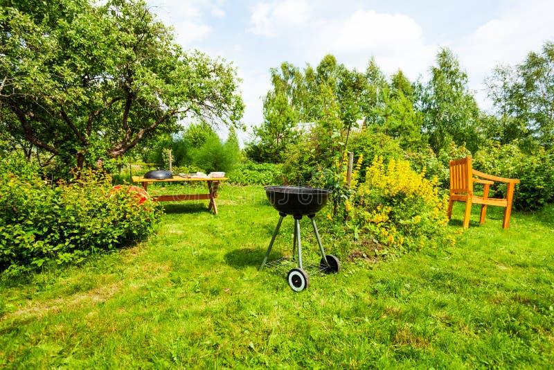 Hermosa vista en jardín con la parrilla, tabla, silla fotografía de archivo