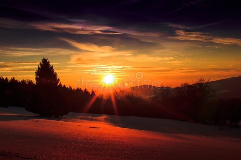 hermosa vista sobre un paisaje nevoso con una puesta del sol brillante foto de archivo