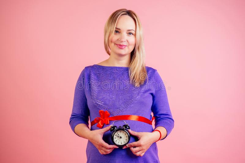 Hermosa y sonriente mujer embarazada de color rubio con un vestido púrpura y un arco de satén rojo en la muñeca de bebé sosten fotografía de archivo