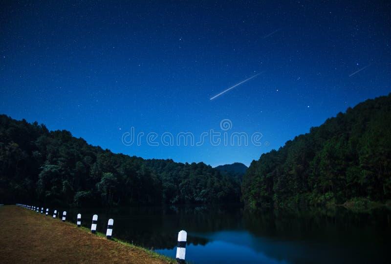 Hermosas vistas de la naturaleza en la noche con la estrella fugaz en la presa septentrional de Tailandia fotos de archivo libres de regalías