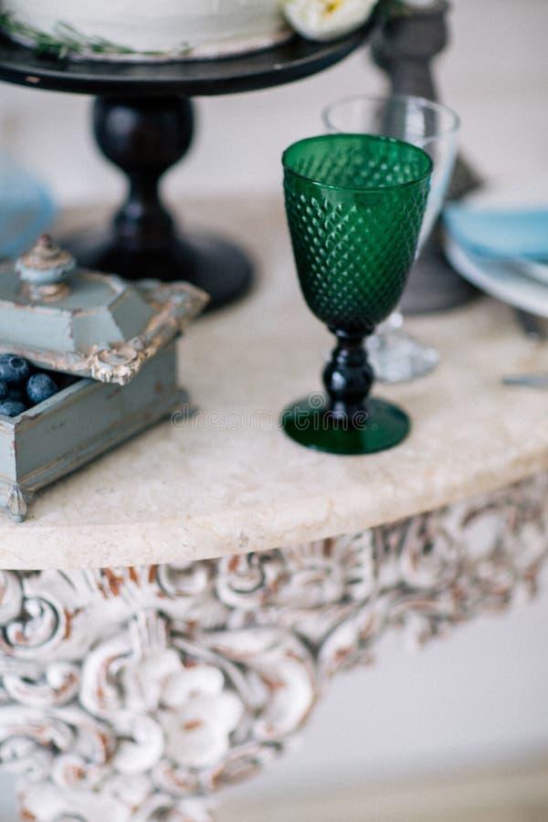 Hermoso adorne la tabla con el vidrio, las velas, el florero con las flores y el pastel de bodas en la tabla en estudio foto de archivo libre de regalías
