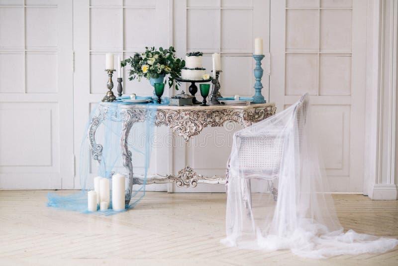 Hermoso adorne la tabla con las velas, el florero con las flores y el pastel de bodas en la tabla en estudio fotografía de archivo libre de regalías