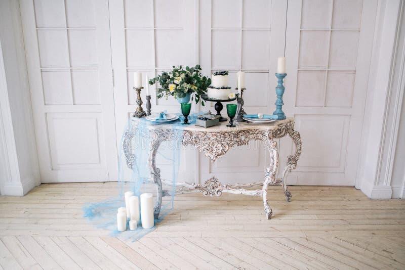 Hermoso adorne la tabla con las velas, el florero con las flores y el pastel de bodas en la tabla en estudio fotos de archivo libres de regalías