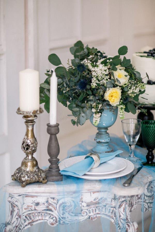 Hermoso adorne la tabla con las velas, el florero con las flores y el pastel de bodas en la tabla en estudio fotos de archivo