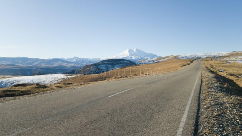 Hermoso camino de asfalto suburbano con marcas Viajes a los lados del monte Elbrus en el Cáucaso Rusia del otoño fotos de archivo