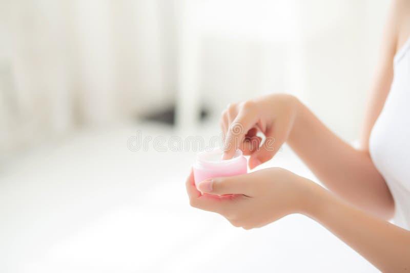Hermoso con la mujer asi?tica de la mano del primer que aplica el producto cosm?tico de la crema del cuidado de piel de la crema  imagenes de archivo