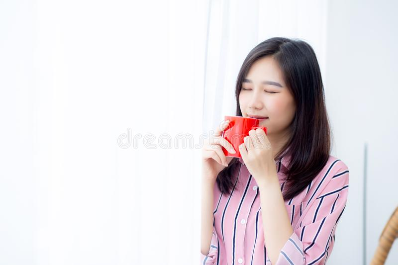 Hermoso de mujer asiática joven del retrato con la bebida a la taza de fondo de la ventana de la cortina de la situación del café imagen de archivo
