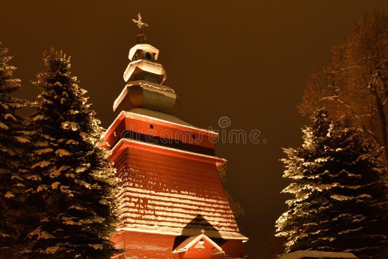 Hermoso iluminado en iglesia de madera de la noche en invierno por completo de la nieve Tylicz Polonia imagen de archivo libre de regalías