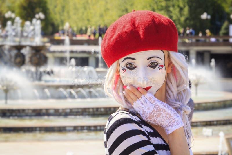 Hermoso imite a la muchacha en una máscara de un payaso triste en un fondo del cielo azul en un día soleado imagen de archivo libre de regalías