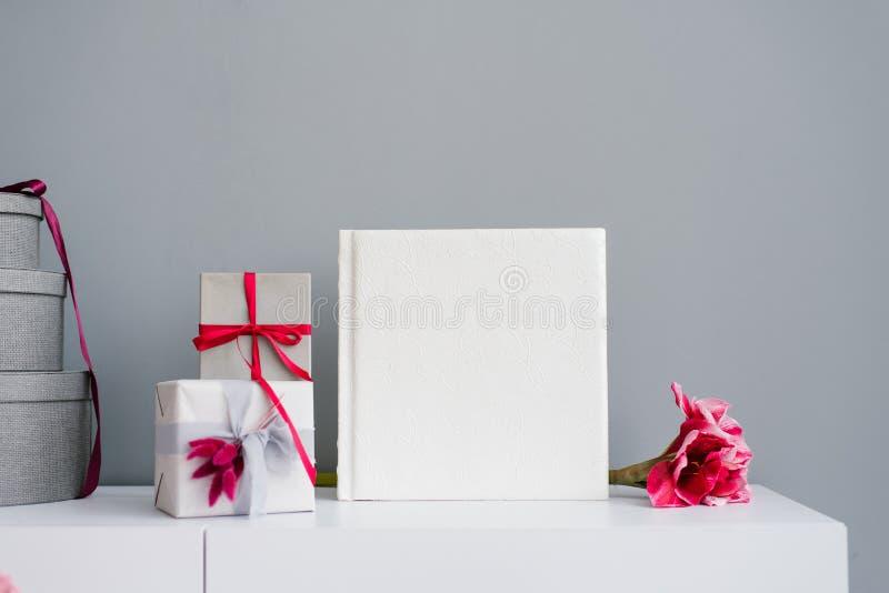 Hermoso libro de fotos de bodas en cuero con encaje grabado rodeado de caja de regalo y estrellas en yeso y tabla foto de archivo libre de regalías