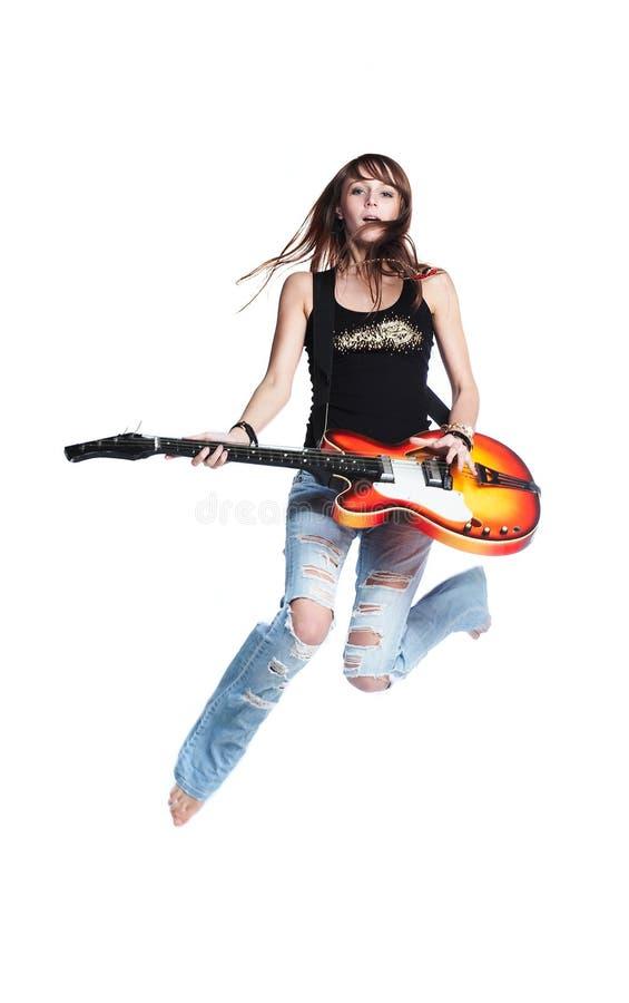 Hermoso roca-n-ruede a la muchacha saltan con la guitarra foto de archivo libre de regalías