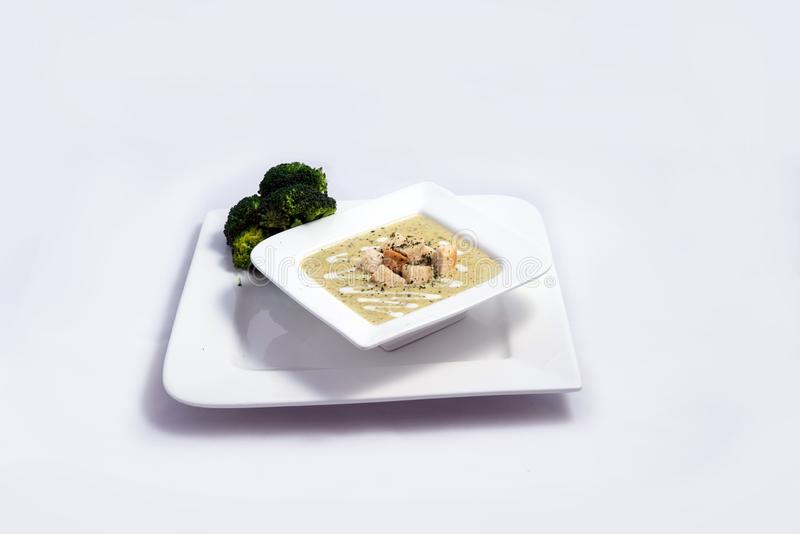 Distant Hero Shot of a Broccoli Soup with bread crumbs, oregano on a minimal white background with a 45 degree front facing angle royalty free stock image