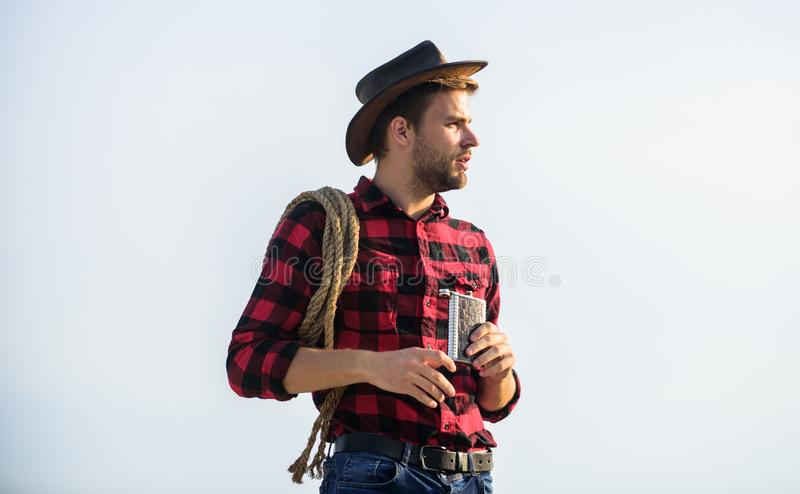 Hero of western culture. Farmer drink water metal flask. Looking for adventures. Farmer cowboy handsome man relaxing. After hard working day at ranch. Lonely royalty free stock photo