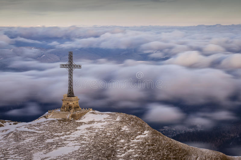 The Heroes Cross of Romania in Bucegi Mountain with clouds movin stock photo