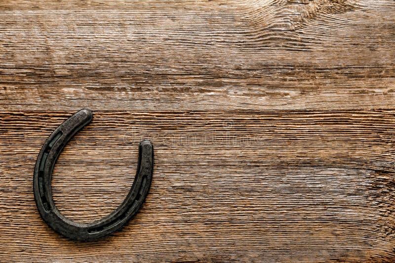 Herradura vieja del metal en fondo de madera antiguo imagen de archivo