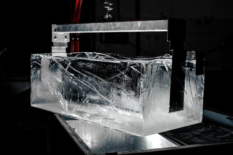 Herramienta de acero que sostiene un cubo de hielo enorme en fondo oscuro de la fábrica moderna foto de archivo libre de regalías