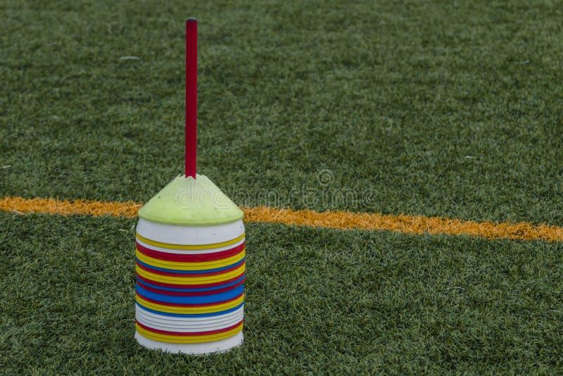Herramienta del cono para entrenar en hierba artificial en academia del fútbol imagenes de archivo