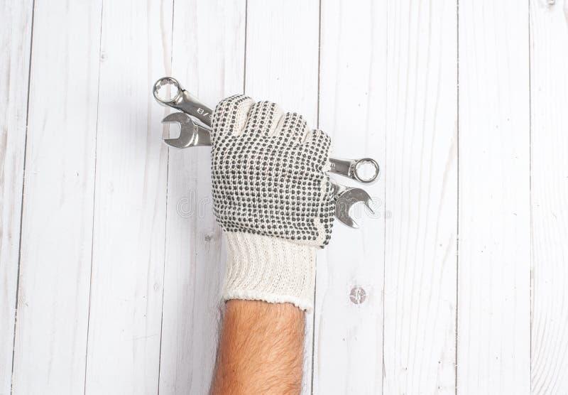 Herramienta La mano en guante est? sosteniendo las llaves en el fondo de madera blanco fotos de archivo