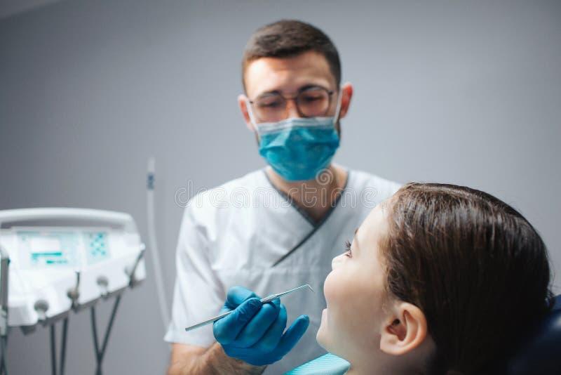 Herramienta masculina cuidadosa del control del dentista a disposición Él mira a la muchacha que se sienta en silla dental en sit fotos de archivo
