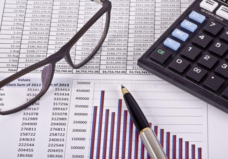 Herramientas, calculadora, pluma y espec. financieras sobre un informe imágenes de archivo libres de regalías
