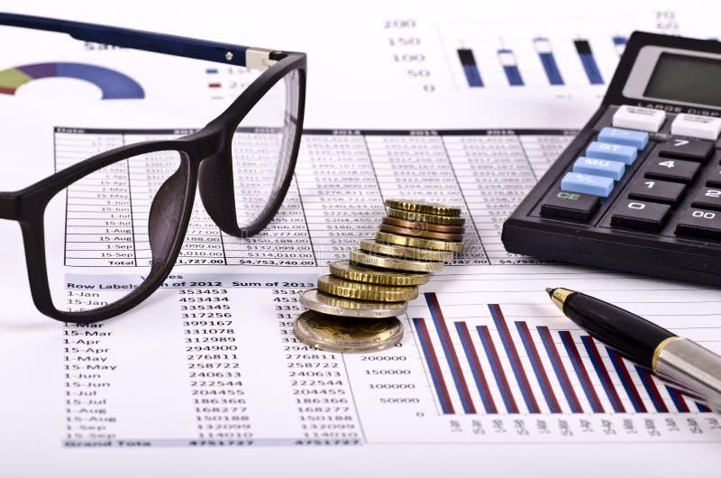 Herramientas, calculadora, pluma y espec. financieras sobre un informe imagenes de archivo